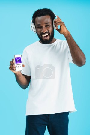 KYIV, UKRAINE - MAY 17, 2019: smiling african american man listening music with headphones and showing smartphone with apple music app, isolated on blue