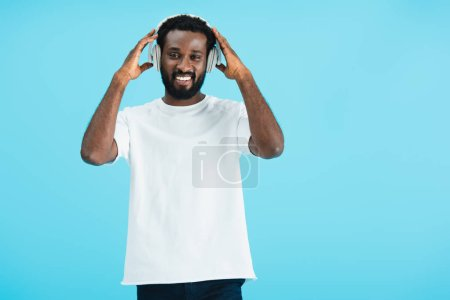 Photo pour Smiling african american man listening music with headphones, isolated on blue - image libre de droit