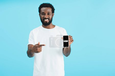 Photo pour KYIV, UKRAINE - 17 MAI 2019 : homme afro-américain souriant pointant du doigt son smartphone avec l'application HBO, isolé sur bleu - image libre de droit