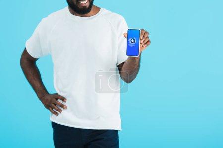 Photo pour KYIV, UKRAINE - 17 MAI 2019 : vue recadrée d'un homme afro-américain montrant un smartphone avec une application shazam, isolé sur bleu - image libre de droit