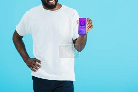 abgeschnittene Ansicht eines afrikanisch-amerikanischen Mannes, der Smartphone mit Shopping-App zeigt, isoliert auf blau