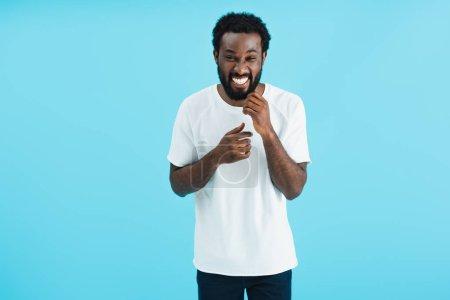 Photo pour Heureux homme afro-américain riant isolé sur bleu - image libre de droit