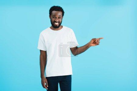 Photo pour Heureux homme afro-américain pointant isolé sur bleu - image libre de droit