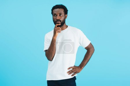 Foto de Thoughtful african american man in white t-shirt isolated on blue - Imagen libre de derechos