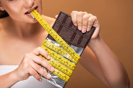 Photo for Partial view of young woman holding yellow measuring tape in mouth and chocolate bar isolated on beige - Royalty Free Image