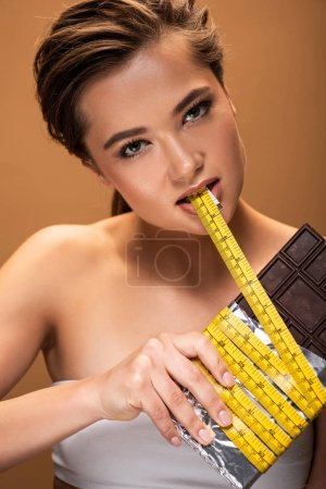 Photo for Young woman holding chocolate bar and yellow measuring tape in mouth isolated on beige - Royalty Free Image