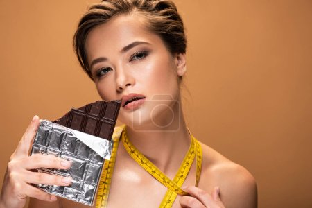 Photo for Nude young woman with yellow measuring tape holding chocolate bar isolated on beige - Royalty Free Image