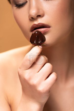 Photo for Young naked woman looking at strawberry in melted chocolate isolated on beige - Royalty Free Image