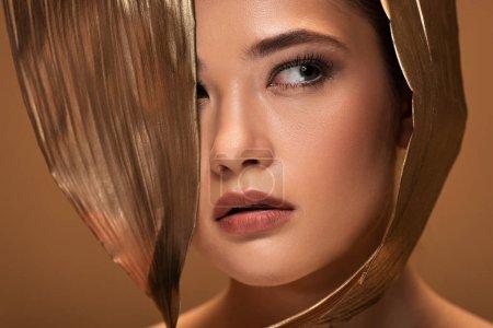 Foto de Portrait of beautiful young woman with decorative golden leaves looking away isolated on beige - Imagen libre de derechos