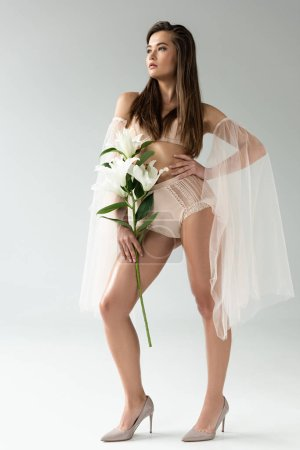tender young woman in beige lingerie and mesh sleeves holding flowers with hand on hip