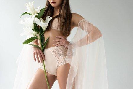 Photo pour Vue partielle de jeune femme tendre dans la lingerie beige et les manches de maille avec des lis posant avec la main sur la hanche d'isolement sur le blanc - image libre de droit