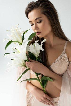 Photo pour Jeune femme tendre dans la lingerie beige retenant des liles d'isolement sur le blanc - image libre de droit