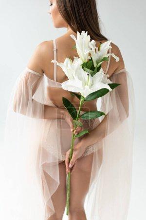 Photo pour Jeune femme délicate dans la lingerie beige et les manches de maille retenant le bouquet des lés d'isolement sur le blanc - image libre de droit