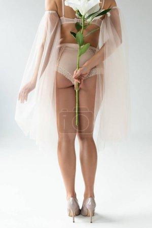 Photo pour Vue recadrée de jeune femme délicate dans la lingerie beige et les manches de maille retenant le bouquet des lés d'isolement sur le blanc - image libre de droit