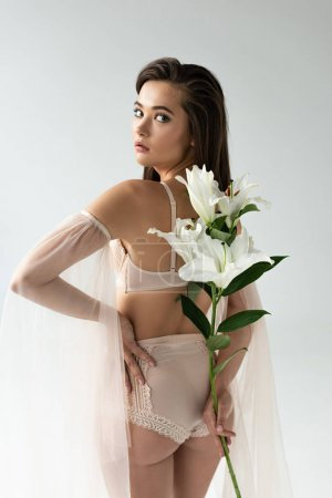 tender young woman in beige lingerie and mesh sleeves holding lilies behind back isolated on white