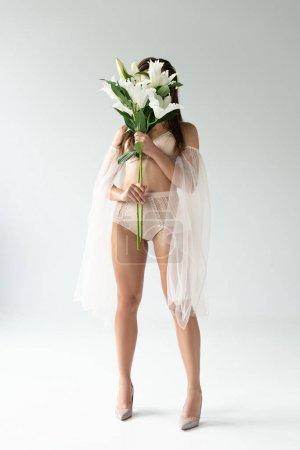 Photo pour Jeune femme tendre dans la lingerie beige et les manches de maille retenant des lildevant du visage sur le blanc - image libre de droit