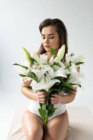 Photo pour Jeune femme tendre dans le body blanc de dentelle retenant des lés retiens avec les yeux fermés isolés sur le blanc - image libre de droit