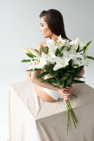 Photo pour Vue arrière de jeune femme tendre dans le corps blanc de dentelle retenant le bouquet des lis d'isolement sur le blanc - image libre de droit