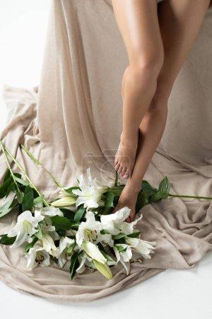 Photo pour Vue recadrée des jambes femelles sur le tissu beige avec les lis dispersés isolés sur le blanc - image libre de droit