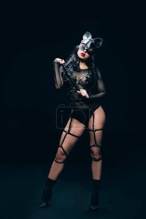 Photo pour Femme brune chaude passionnée en costume bdsm et masque avec fouet flagellation sur fond noir - image libre de droit