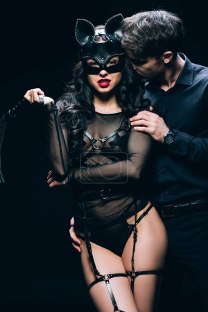 Photo pour Jeune homme baisers sexy brunette femme avec fouet fouet isolé sur noir - image libre de droit