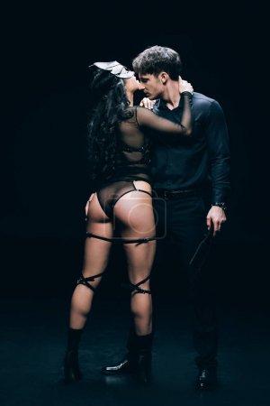 Photo pour Sexy jeune femme en bdsm costume femme près de l'homme avec fessée pagaie isolé sur noir - image libre de droit