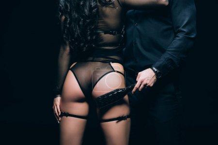 Photo pour Vue recadrée des fesses sexy sur la femme près de l'homme avec bdsm fessée pagaie isolé sur noir - image libre de droit
