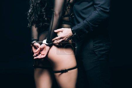 Photo pour Vue recadrée de l'homme debout près de femme sexy menottes isolées sur noir - image libre de droit