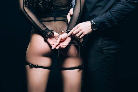 Photo pour Vue partielle de l'homme debout près de la femme dans les menottes et sexy bdsm costume isolé sur noir - image libre de droit