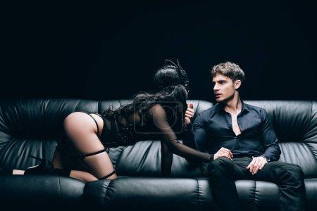 Photo pour Sexy brunette femme en bdsm costume tentant homme sur canapé en cuir noir isolé sur noir - image libre de droit