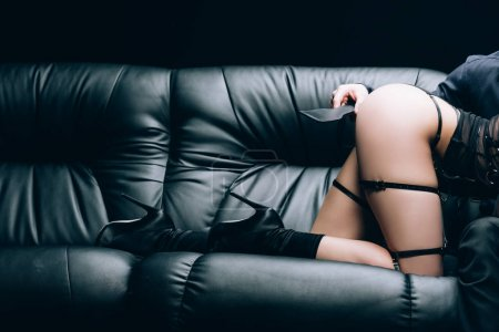 Photo pour Vue partielle de l'homme tenant bdsm fessée pagaie près de femme sexy en chaussures à talons sur canapé en cuir noir isolé sur noir - image libre de droit