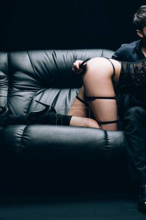 Photo pour Vue recadrée de l'homme tenant bdsm fessée pagaie près de femme sexy sur canapé en cuir noir isolé sur noir - image libre de droit
