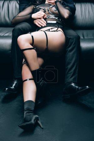 Photo pour Vue recadrée de femme sexy en costume bdsm couché om homme sur canapé en cuir noir - image libre de droit