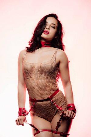 Foto de Sexy mujer joven en lencería beige, cuello rojo tocando cinturón de espada sobre fondo claro - Imagen libre de derechos