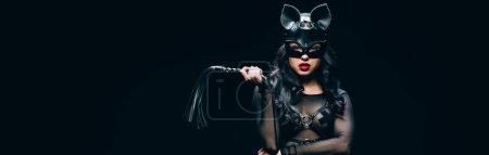 Photo pour Plan panoramique de jeune femme brune sexy en costume bdsm et masque avec fouet fouet en cuir isolé sur noir - image libre de droit
