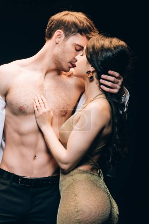 Photo for Young brunette woman kissing boyfriend with bare muscular torso isolated on black - Royalty Free Image