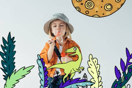 Foto de Cute kid in hat and orange shirt blowing soap bubbles with dinosaur walking among plants fairy illustration isolated on grey - Imagen libre de derechos
