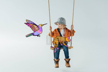 Foto de Cute kid in jeans and orange shirt sitting on swing with fantasy cat on knees and looking at colorful bird illustration on grey background - Imagen libre de derechos