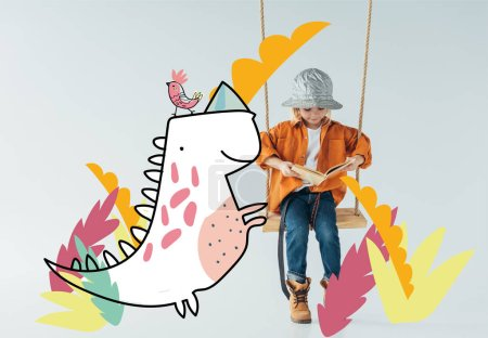 Foto de Cute kid in jeans and orange shirt sitting on swing and reading book on grey background with fantasy bird and dinosaur illustration - Imagen libre de derechos