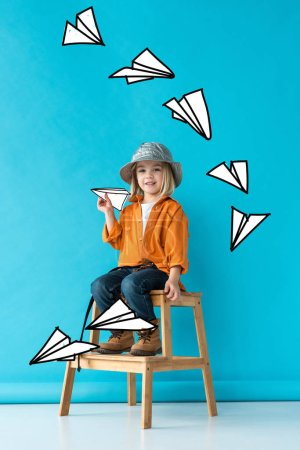 Foto de Kid in jeans and orange shirt sitting on stairs and playing with fairy paper planes - Imagen libre de derechos