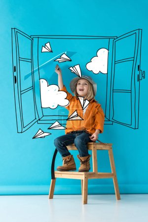 Photo pour Excited kid in jeans and orange shirt sitting on stairs and playing with blue paper plane on blue background with fairy white window, paper planes and clouds illustration - image libre de droit