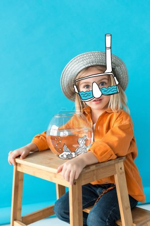 Photo for Kid in silver hat, orange shirt and snorkel sitting on stairs with fairy fish in aquarium on blue background - Royalty Free Image