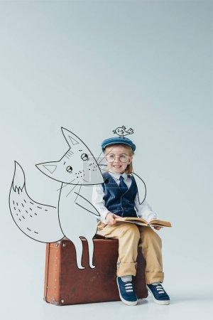 Photo pour Gosse de sourire dans le gilet rétro avec l'oiseau de fantaisie sur le chapeau s'asseyant sur la valise près du renard de fée et du livre de fixation sur le fond gris - image libre de droit