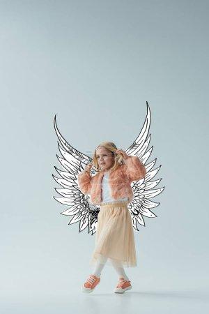 Photo pour Mignon enfant en fausse fourrure manteau et jupe avec des ailes d'ange de fée marchant et regardant loin sur fond gris - image libre de droit