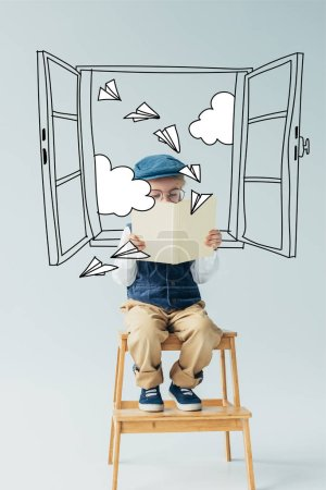 Foto de Cute kid sitting on wooden stairs and reading book on grey background with fairy window, paper planes and clouds illustration - Imagen libre de derechos