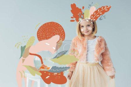 Photo pour Enfant adorable dans le manteau et la jupe de fausse fourrure regardant l'appareil-photo et restant près de la table avec le fishbowl d'isolement sur le gris avec l'illustration orange de nature de fée - image libre de droit