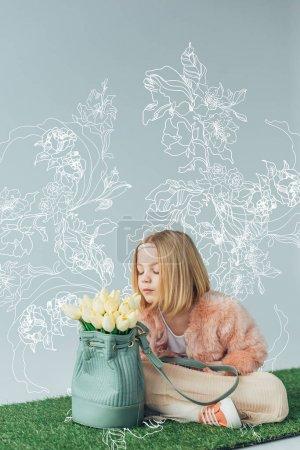 Photo pour Mignon enfant avec les jambes croisées sentant tulipes blanches dans le sac isolé sur gris avec des fleurs blanches illustration - image libre de droit