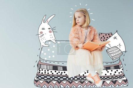 Photo pour Enfant rêveur en fausse fourrure manteau et jupe assis sur un lit fantastique avec des oreillers près du lapin et tenant livre isolé sur gris - image libre de droit
