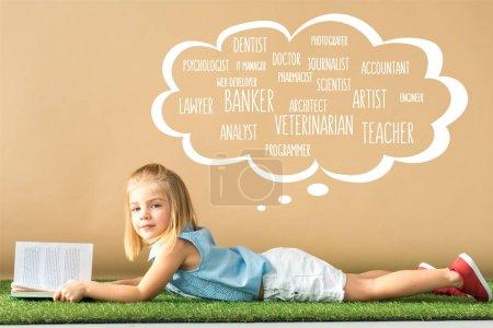 Foto de Lindo niño acostado en la alfombra de hierba y la celebración de libro sobre fondo beige con burbuja de pensamiento blanco con varias profesiones - Imagen libre de derechos