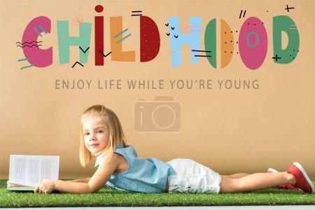 Photo pour Mignon enfant couché sur tapis en herbe et tenant livre sur fond beige avec illustration d'enfance - image libre de droit